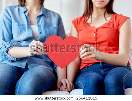 people, homosexuality, same-sex marriage, holidays and love concept - close up of happy lesbian couple holding red paper hearts - stock photo