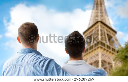 people, homosexuality, same-sex marriage, travel and love concept - close up of happy male gay couple hugging from back over paris eiffel tower background