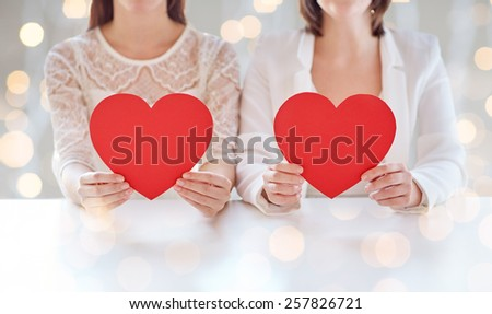 people, homosexuality, same-sex marriage, valentines day and love concept - close up of happy lesbian couple holding red paper hearts over holiday lights background - stock photo