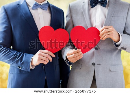 people, homosexuality, same-sex marriage, valentines day and love concept - close up of happy married male gay couple holding red paper heart shapes on wedding over yellow lights background - stock photo