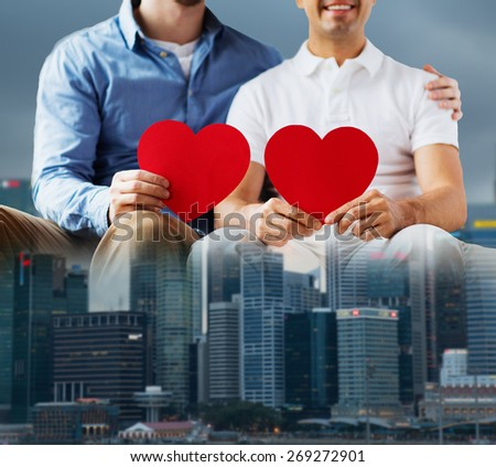 people, homosexuality, same-sex marriage, valentines day and love concept - close up of happy gay male couple with red hearts over city background - stock photo