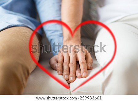 people, homosexuality, same-sex marriage, valentines day and love concept - close up of happy male gay couple holding hands with red heart shape - stock photo