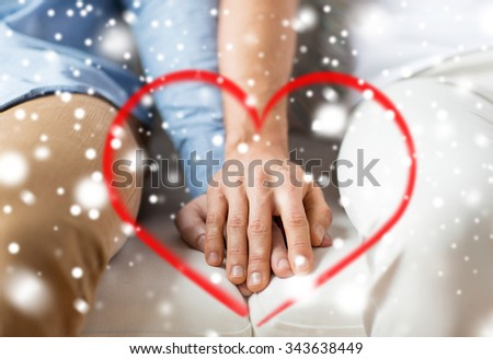 people, homosexuality, same-sex marriage, valentines day and love concept - close up of happy male gay couple holding hands with red heart shape and snow effect - stock photo