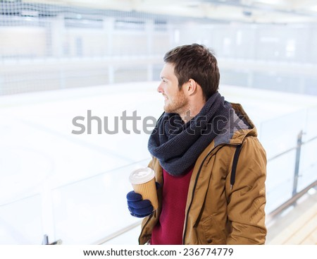 people, hot drinks and leisure concept - happy young man with paper coffee cup on skating rink - stock photo