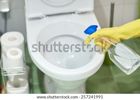 people, housework and housekeeping concept - close up of hand in rubber glove with detergent cleaning toilet pan