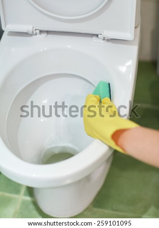 people, housework and housekeeping concept - close up of hand in rubber glove with detergent cleaning toilet pan - stock photo