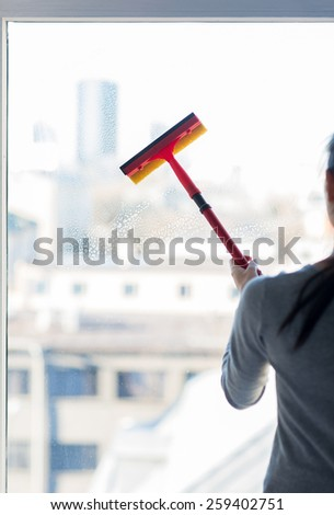 people, housework and housekeeping concept -close up of woman cleaning window with sponge mop - stock photo