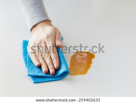 people, housework and housekeeping concept - close up of woman hand cleaning dirty table surface with cloth at home - stock photo