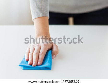 people, housework and housekeeping concept - close up of woman hand cleaning table with cloth at home - stock photo