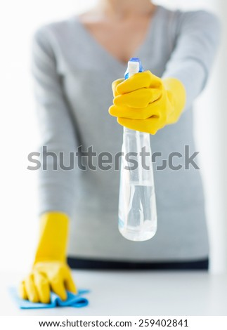 people, housework and housekeeping concept - close up of woman hands cleaning table with cloth and detergent spray at home - stock photo