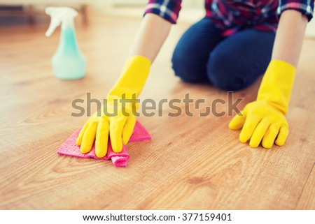 people, housework and housekeeping concept - close up of woman in rubber glover with cloth and detergent spray cleaning floor at home - stock photo