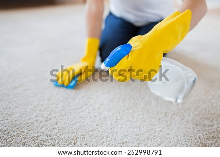 people, housework and housekeeping concept - close up of woman in rubber gloves with cloth and detergent spray cleaning carpet at home