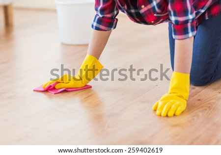 people, housework and housekeeping concept - close up of woman in rubber gloves with cloth cleaning floor at home