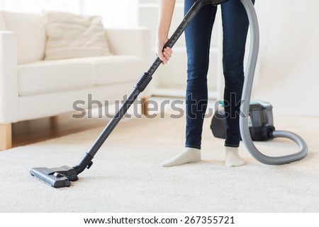 people, housework and housekeeping concept - close up of woman with legs vacuum cleaner cleaning carpet at home - stock photo