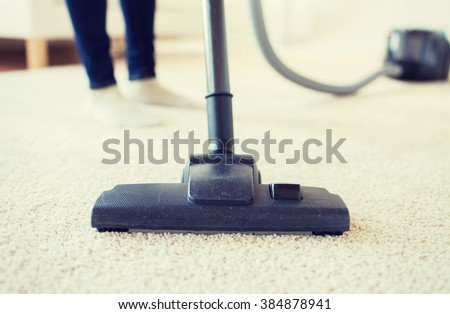 people, housework and housekeeping concept - close up of woman with legs vacuum cleaner cleaning carpet at home