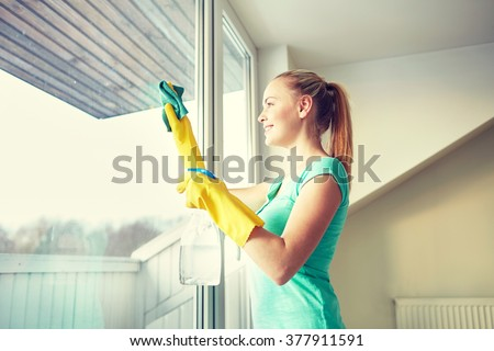 people, housework and housekeeping concept - happy woman in gloves cleaning window with rag and cleanser spray at home - stock photo
