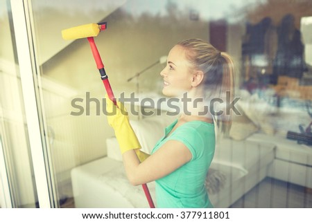 people, housework and housekeeping concept - happy woman in gloves cleaning window with sponge mop at home - stock photo