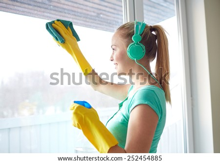 people, housework and housekeeping concept - happy woman in headphones listening to music and cleaning window with cleanser at home - stock photo