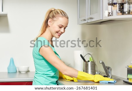 people, housework and housekeeping concept - happy woman in protective gloves cleaning table with rag at home kitchen - stock photo