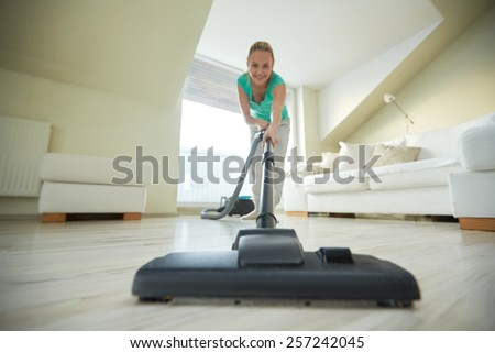 people, housework and housekeeping concept - happy woman with vacuum cleaner at home - stock photo