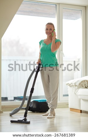 people, housework and housekeeping concept - happy woman with vacuum cleaner calling on smartphone at home - stock photo