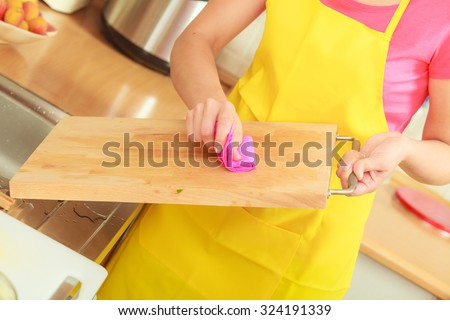 People, housework and housekeeping concept. Woman doing the tidying up in kitchen cleaning wooden cutting board with rag sponge - stock photo