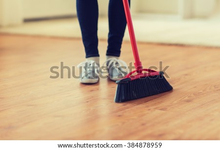 people, housework, cleaning and housekeeping concept - close up of woman legs with broom sweeping floor at home - stock photo