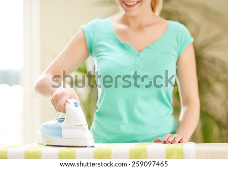 people, housework, laundry and housekeeping concept - close up of happy woman with iron and ironing board at home - stock photo