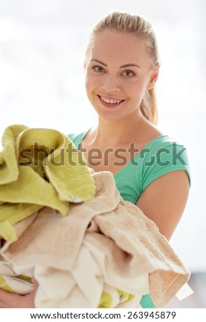 people, housework, laundry and housekeeping concept - happy woman carrying washed clothes at home - stock photo