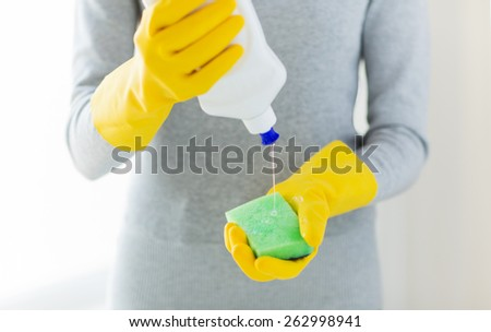 people, housework, washing-up and housekeeping concept - close up of woman applying liquid soap from cleanser bottle to sponge at home
