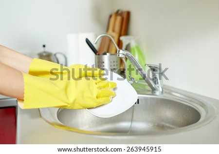 people, housework, washing-up and housekeeping concept - close up of woman hands in protective gloves washing dishes with sponge at home kitchen - stock photo