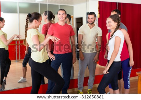 People in a dancing school are looking at their trainer and smiling - stock photo