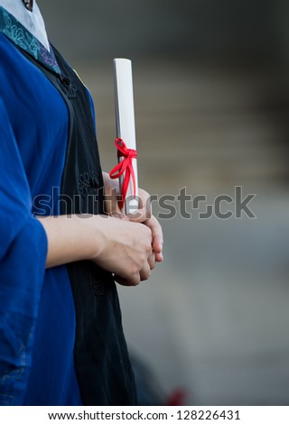 people in a gown holding a diploma. - stock photo