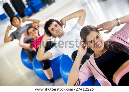 People in a gym class doing sit-ups - stock photo