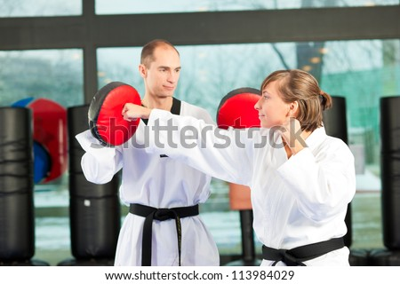 People in a gym in martial arts training exercising Taekwondo, both have a black belt - stock photo