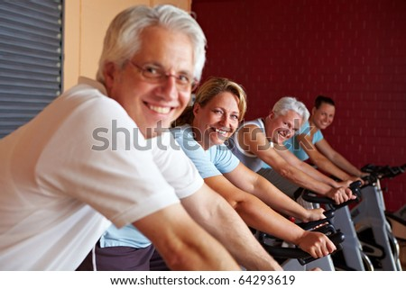 People in a gym sitting on bikes - stock photo
