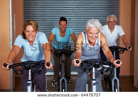 People in a gym sitting on bikes