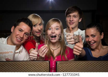 People in a movie theater having fun, laughing and showing thumbs up - stock photo