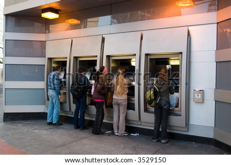 People in ATM from the side - stock photo
