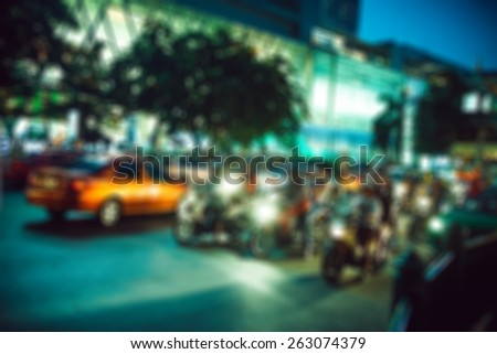 people in bokeh, street of night Bangkok, motorcyclists on city road