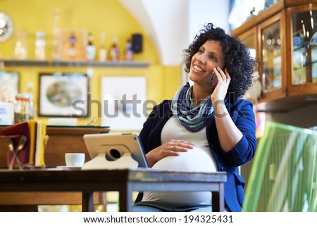 People in cafeteria, with pregnant woman drinking espresso coffee sitting at table talking on phone - stock photo