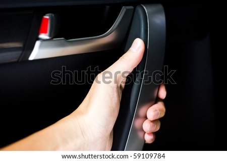 people in car gripping the handle of car door. - stock photo