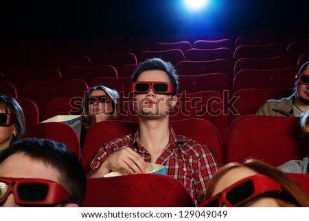 People in 3D glasses watching movie in cinema - stock photo