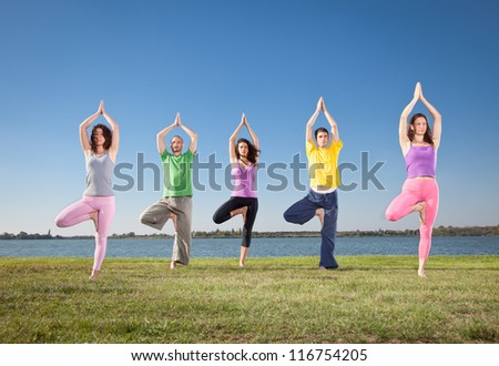 People in group  practice Yoga asana on lakeside. Yoga concept. - stock photo