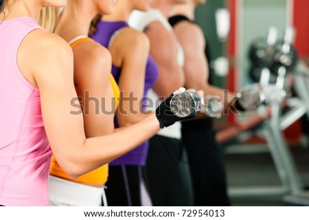 People in gym or fitness club exercising with dumbbells together