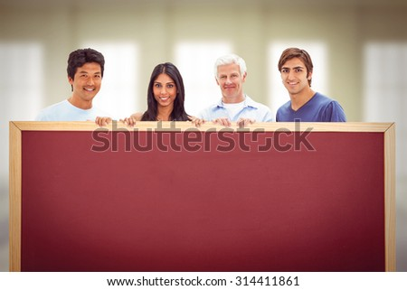 People in jeans holding a big sign against room with windows