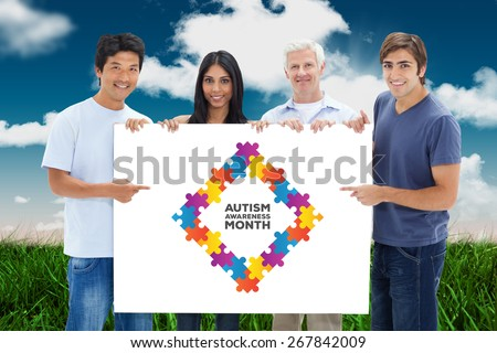People in jeans holding and showing a big sign against field and sky - stock photo