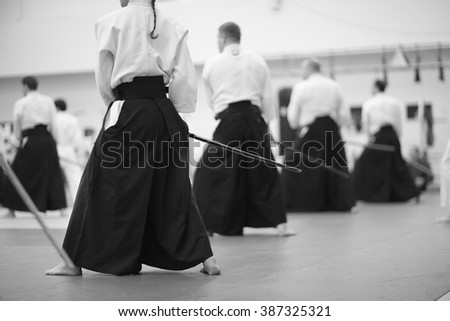People in kimono and hakama standing and practicing sword technique - stock photo