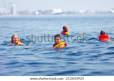 people in life jackets swimming in open sea - stock photo