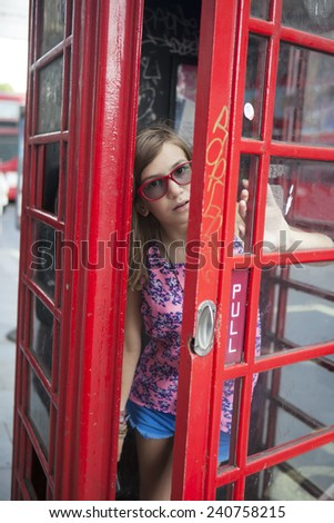 People in London- girl by red phone booth. Portrait of beautiful smiling happy young female casual professional business woman walking outside in City of Westminster, London, England, Great Britain. - stock photo